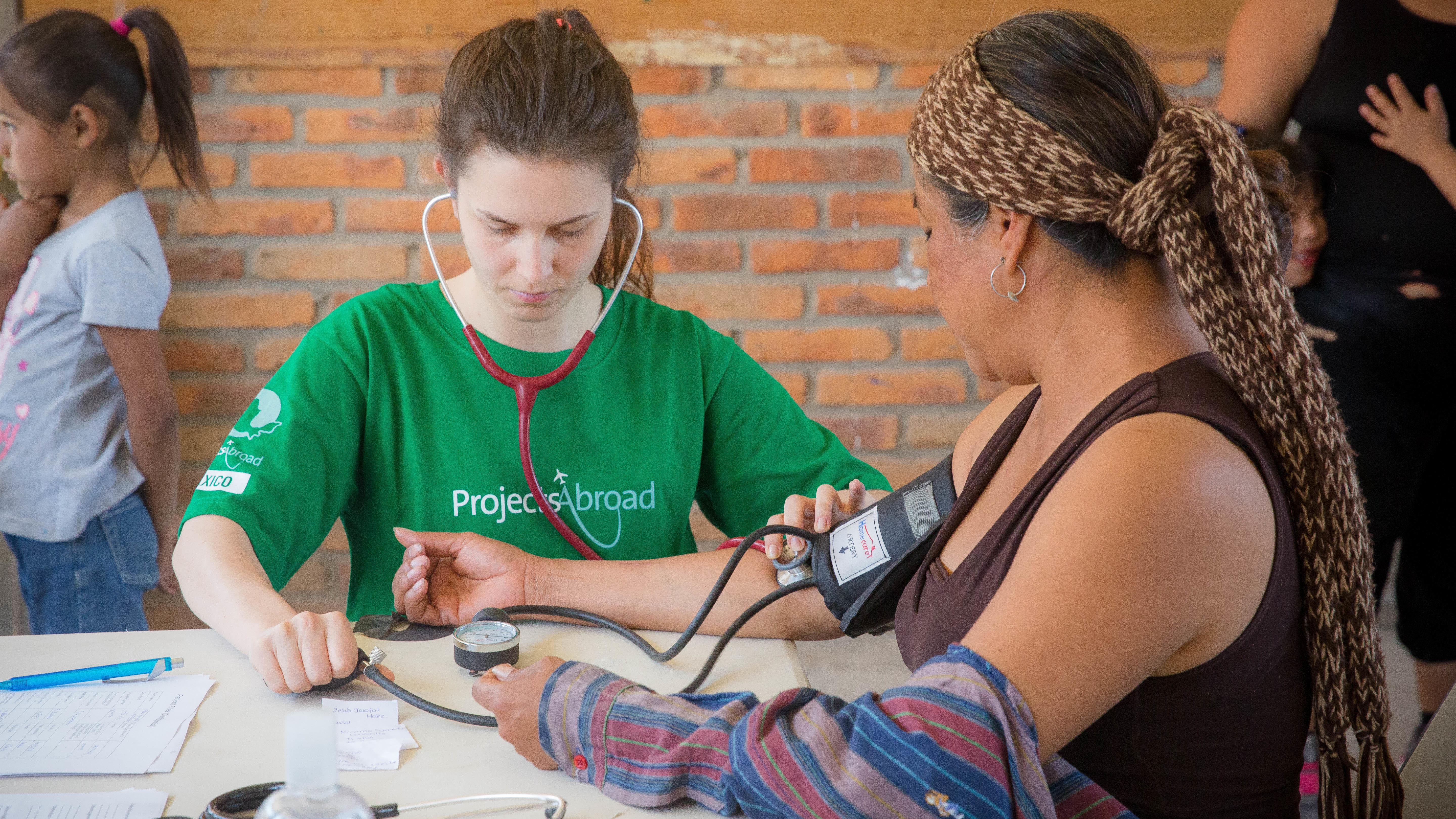 At her Projects Abroad Public Health placement for teenagers in Mexico, an intern checks a woman's vital signs.